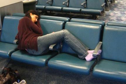Moça tentando dormir nos bancos de um aeroporto no Egito
